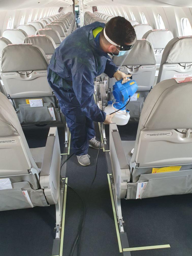 Onet Propreté - Agent de nettoyage en train de désinfecter un avion