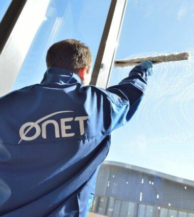 Onet Propreté et Services - Agent de nettoyage en train de faire les vitres d'une entreprises