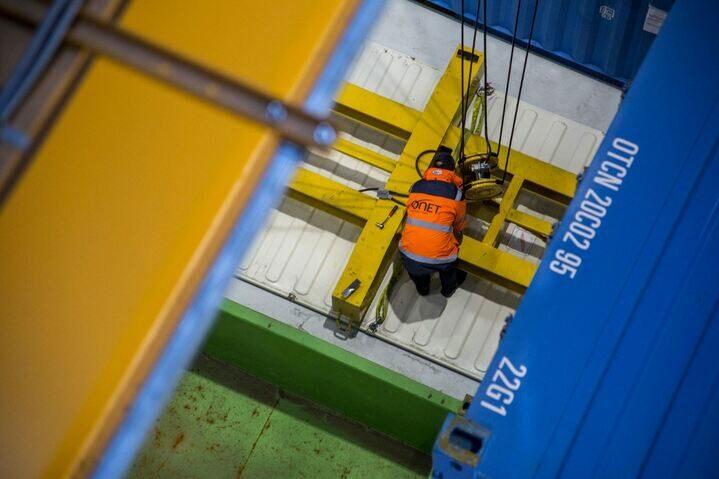Un agent Onet Technologies positionne les câbles pour qui permettront de déplacer les conteneurs dans le hangar de stock Sogeval - Zone de stockage